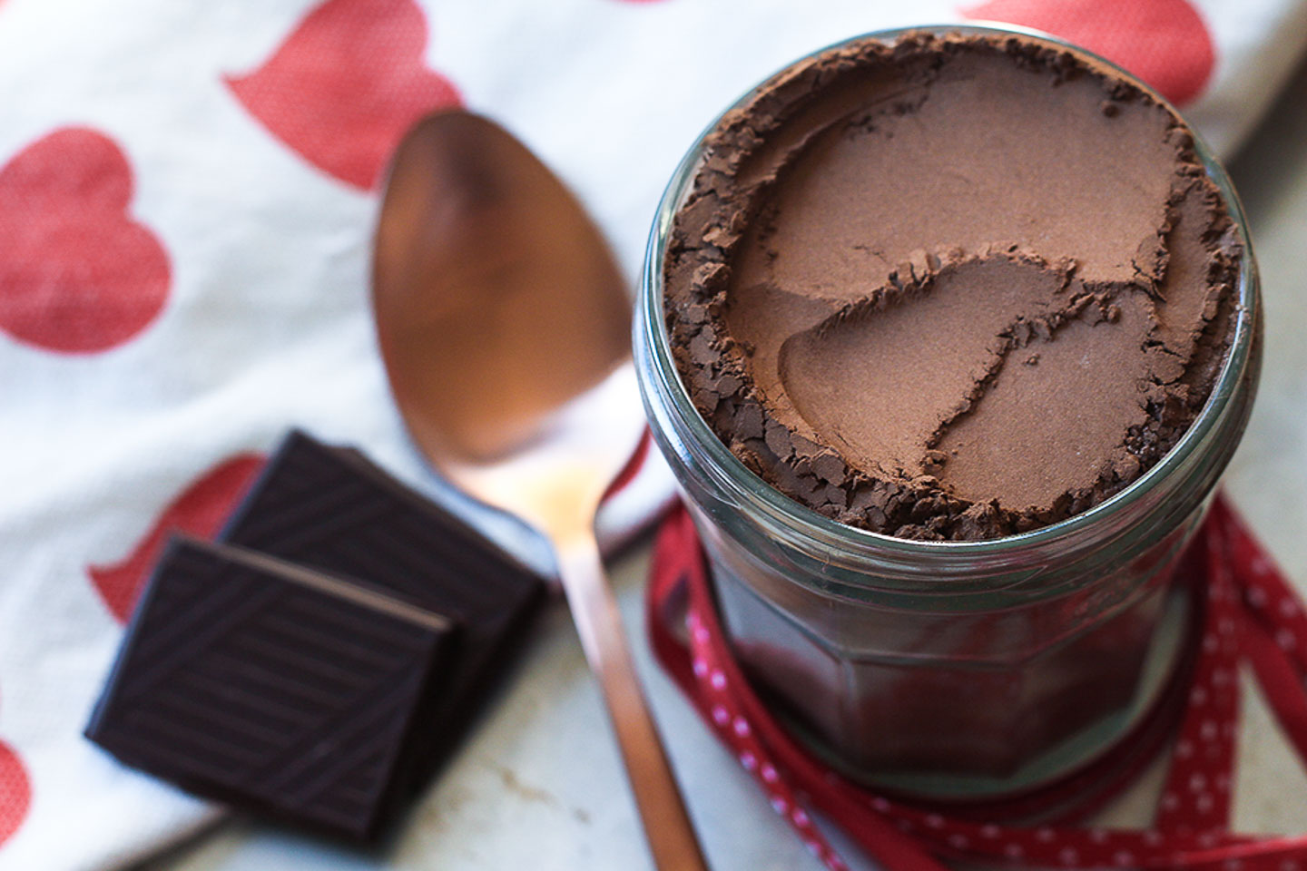 Luxe hot chocolate mixture in a jar with serving spoon.