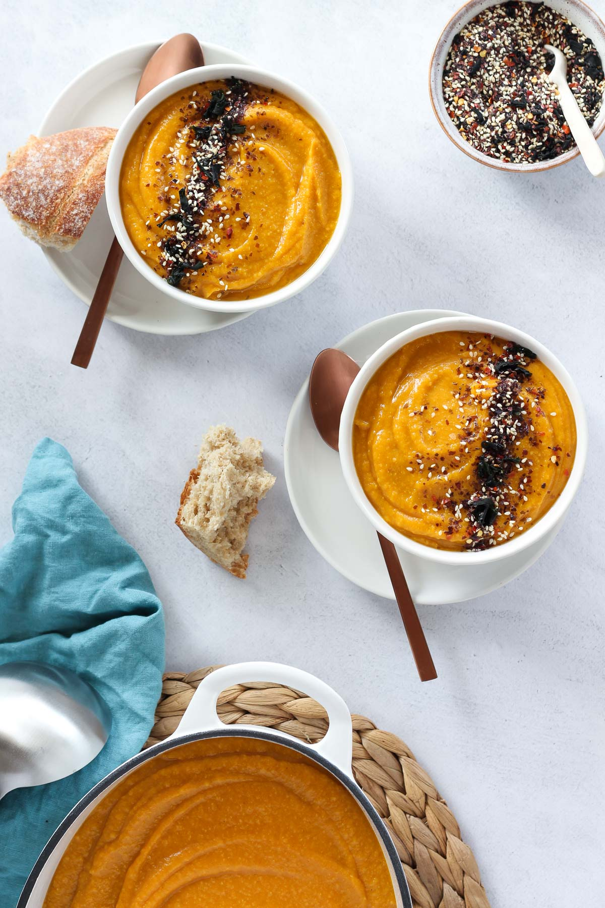 Bowls of pumpkin soup with crusty bread, furikake seasoning and larger pot of soup