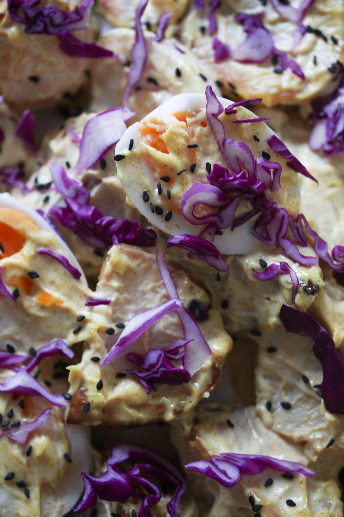 Close up of Japanese Curried Potato and Egg Salad, garnished with red cabbage, black sesame seeds