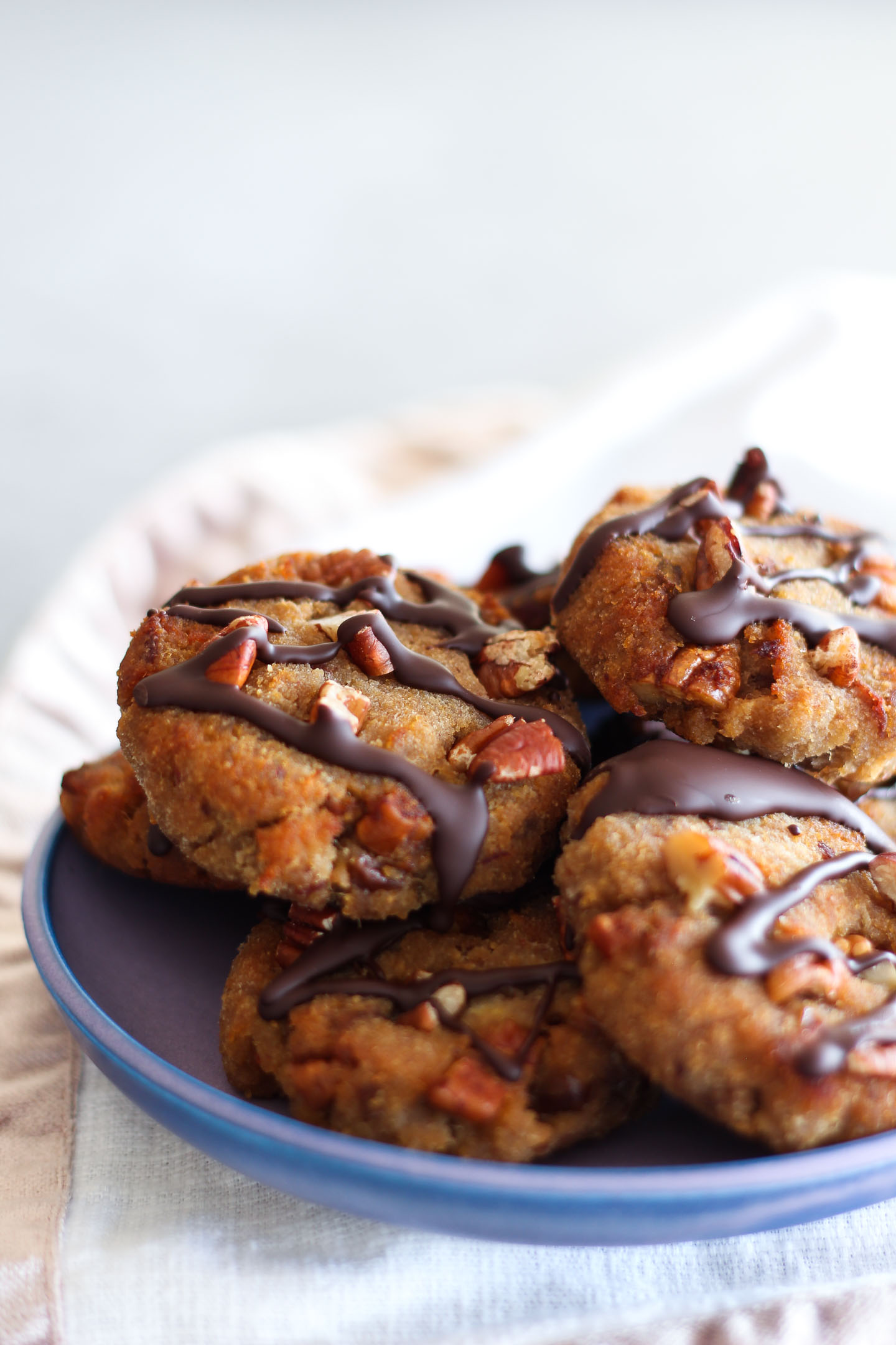 Banana, Date and Pecan Collagen Cookies drizzled with chocolate and piled high on a plate