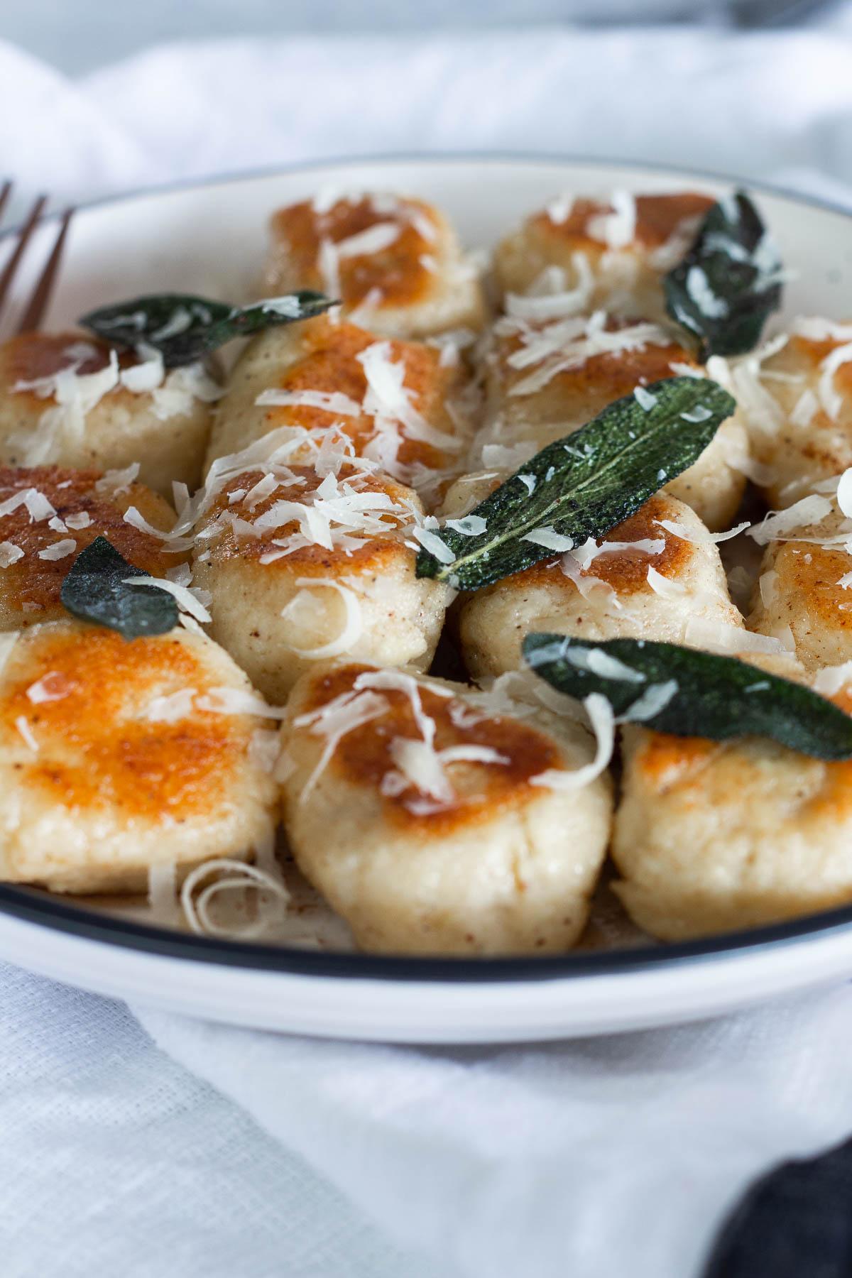 Close up shot of Ricotta Gnocchi with Crispy Sage and Parmesan
