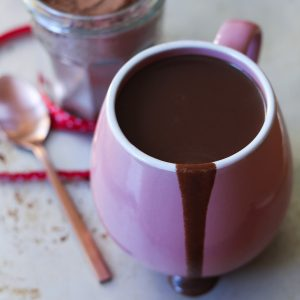 Close up image of hot chocolate in an oversized pink mug, with a drizzle down the side.