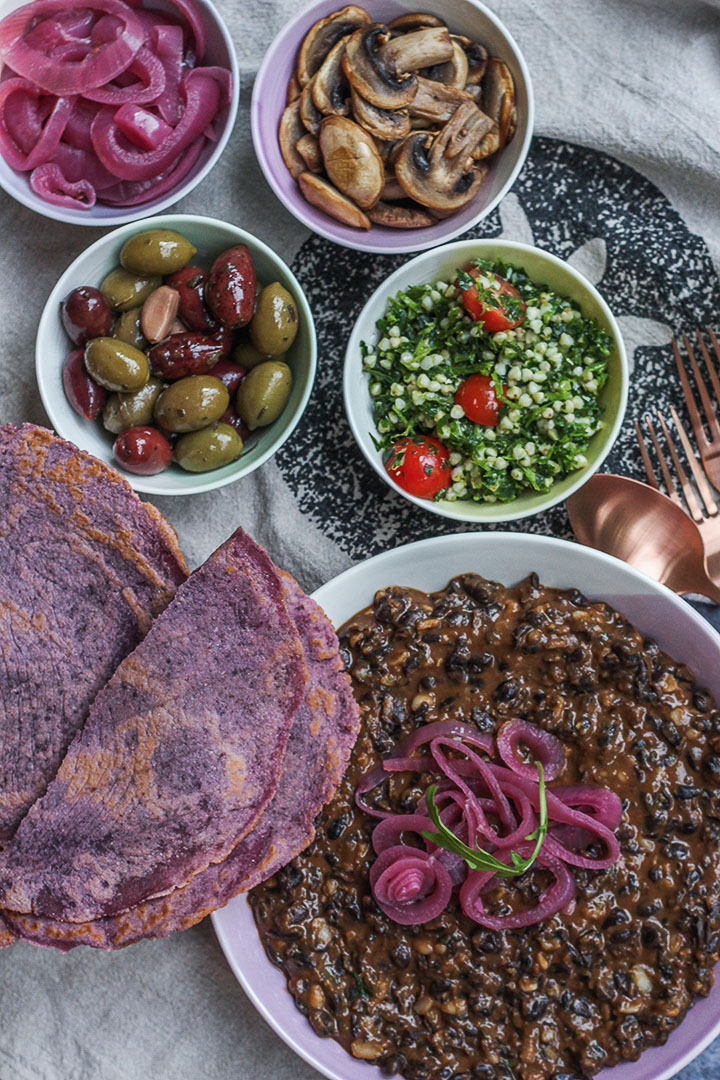 Refried Black Beans served with pickled red onions, browned mushrooms, mixed olives and tabouleh
