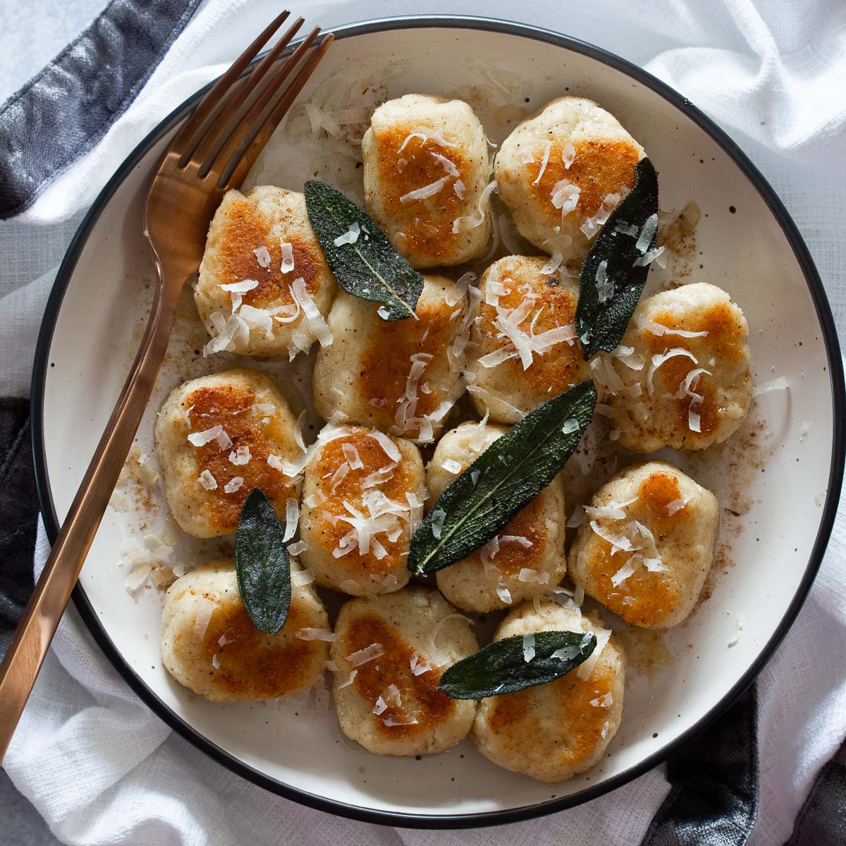 Ricotta gnocchi plated and garnished with crispy sage leaves and fresh grated parmesan