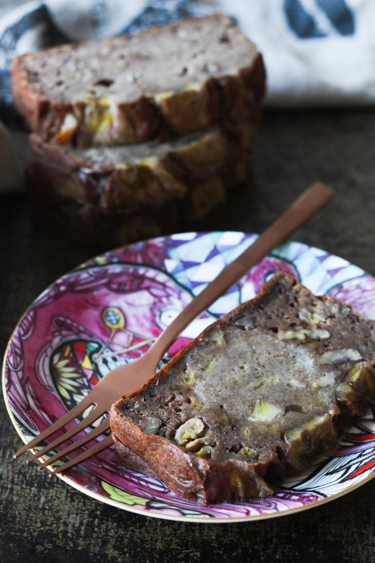 Banana bread served on a decorative plate with slices in the background
