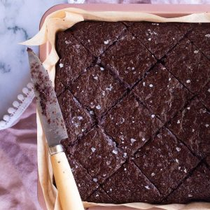 Miracle Flourless Brownies freshly cut in a diamond shape and sprinkled with sea salt