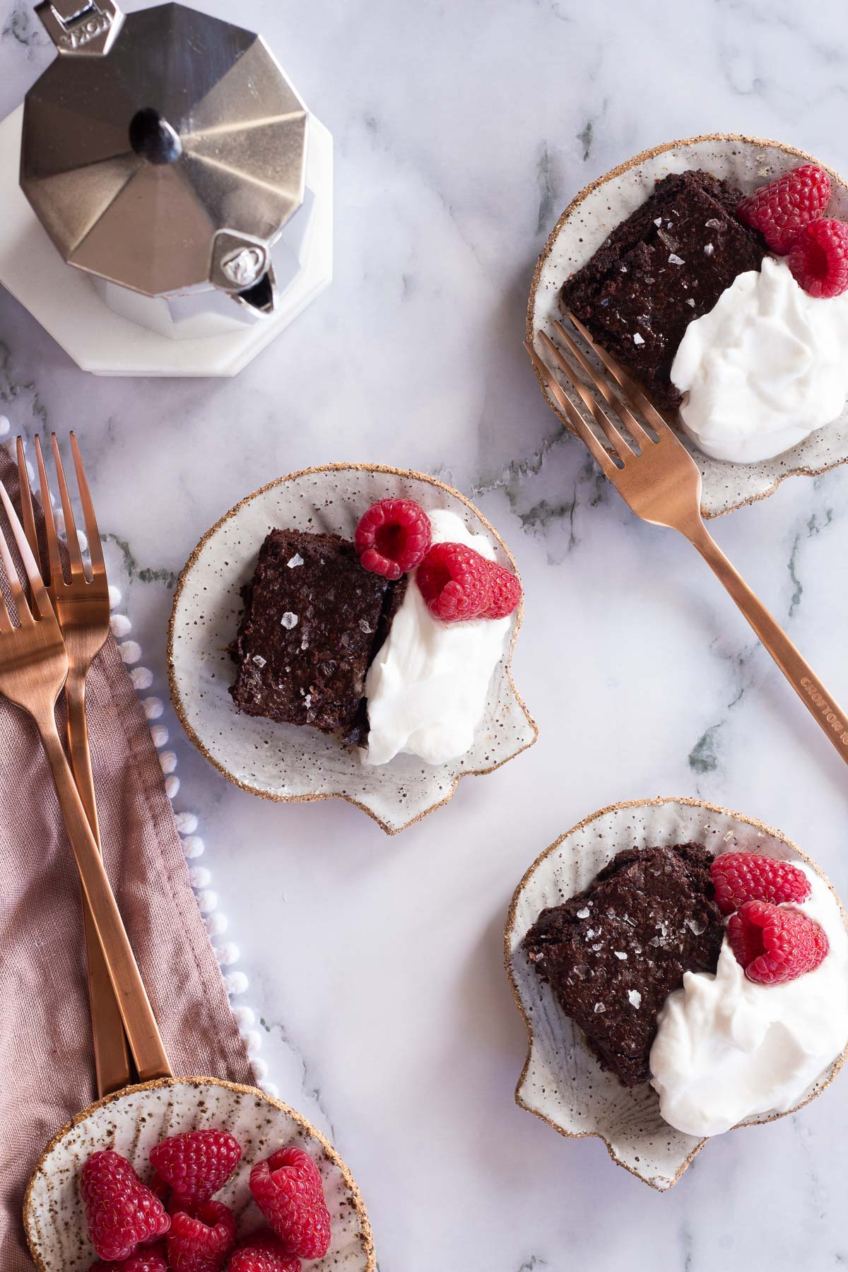 Miracle Flourless Brownies cut and served with coffee, cream and raspberries