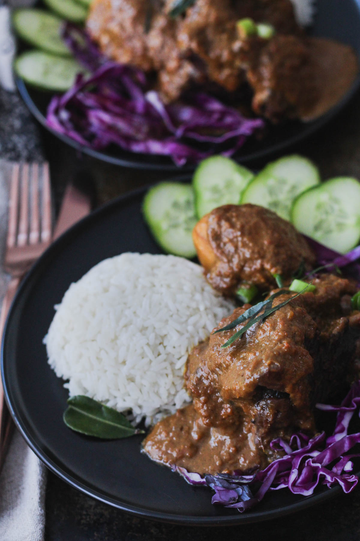 Beef Cheek Rendang served with white rice, sliced cucumbers and shredded red cabbage