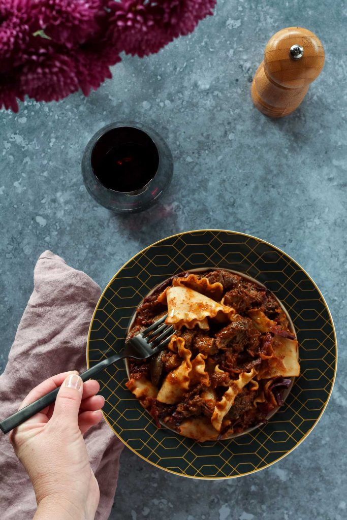 Beef Cheek Ragu served with red wine, with a beautiful table setting.