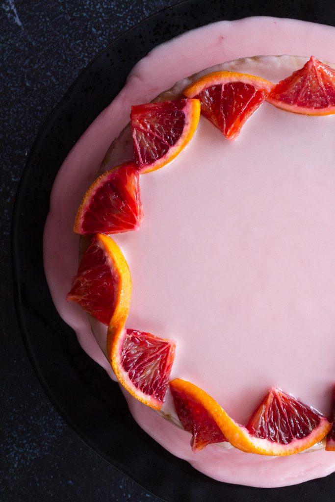 Close up shot of Whole Blood Orange Cake with glaze and blood orange decoration
